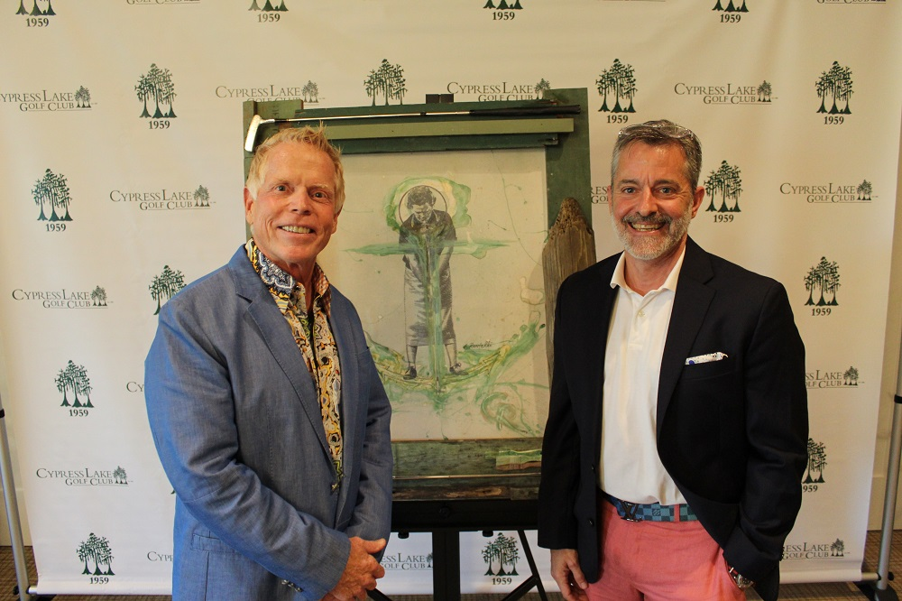2 men standing in front of a piece of art smiling